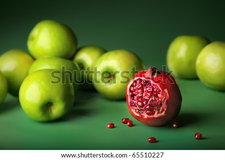 Still-life of pomegranate with green apples on darkly green background, different concepts - red pomegranate before green apples. Color contrast - stock photo