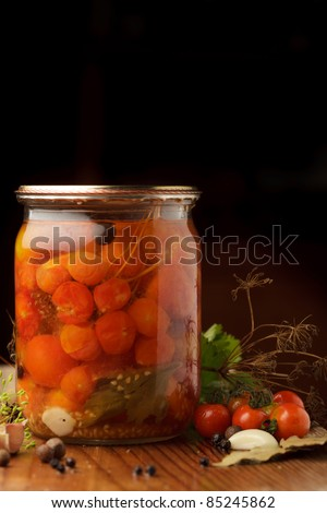 Still life of preserving tomatoes on wooden table in kitchen - stock photo