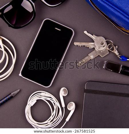 Still life of random objects of modern girl / woman. Handbag, keys, cellphone, sunglasses, earphones, black nail polish, leather bracelet, paper notepad, pen. Dark gray background. Aerial view. - stock photo