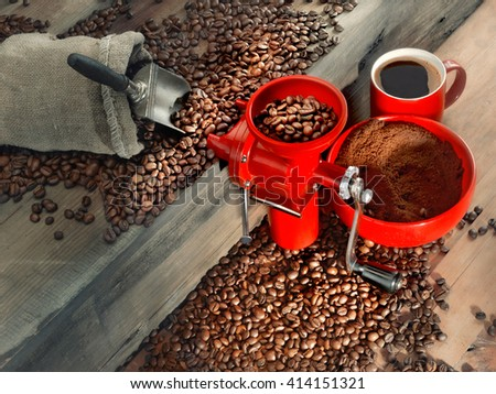 Still-life of red stylish coffee mill and coffee beans on wooden table - stock photo