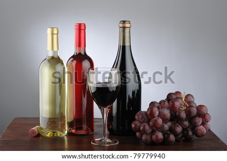 Still life of red wine, white, rose, glass of wine, grapes, bottle and cork - stock photo