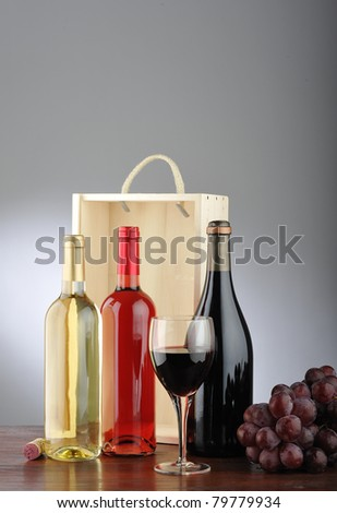 Still life of red wine, white, rose, glass of wine, grapes, bottle and cork with wooden box behind - stock photo