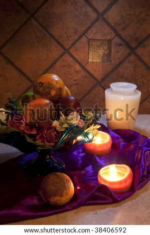 still life of rotten fruit in bowl and candles - stock photo