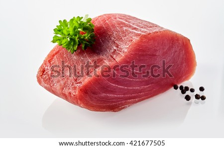 Still Life of Slab of Raw Tuna Fish on White Background Garnished with Black Peppercorns and Sprig of Fresh Green Herbs - stock photo
