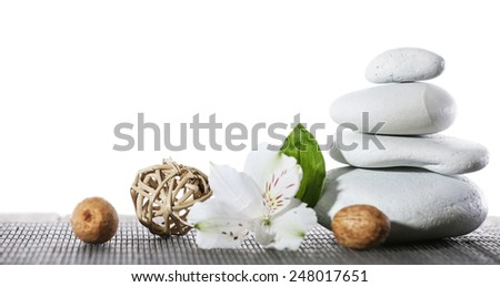 Still life of spa stones on bamboo mat surface isolated on white - stock photo