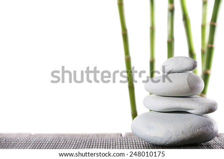Still life of spa stones on bamboo mat surface with bamboo sticks isolated on white - stock photo