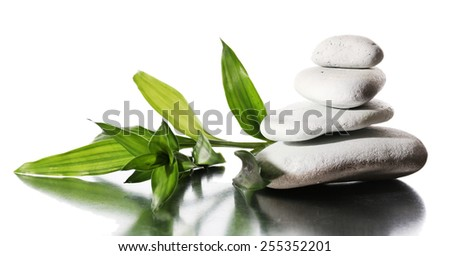 Still life of spa stones on glossy surface isolated on white - stock photo