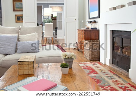 Still life of stylish, personal and elegant home living room with a large white sofa and a fireplace, decorated with quality carpets, house interior. Beautiful design home space family room, indoors. - stock photo