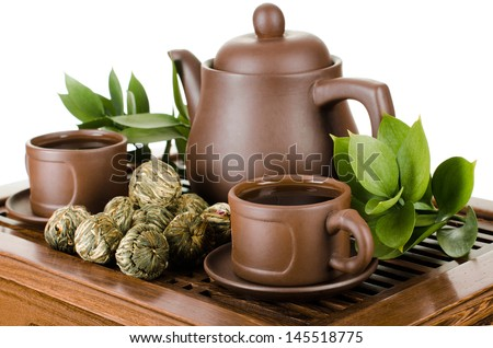 still life of the clay teapot and  cup on wooden trivet,  on white background, isolated - stock photo