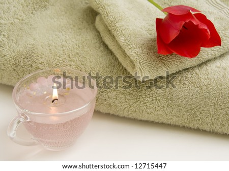 Still life of towel, hand cloth, candle and red tulip. - stock photo