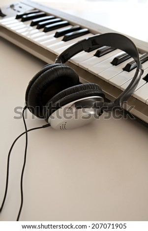 Still life of two electronic music and sound devices laying together on a white desk in a recording studio, interior. Detail view of a pair of headphones and a keyboard, technology.
