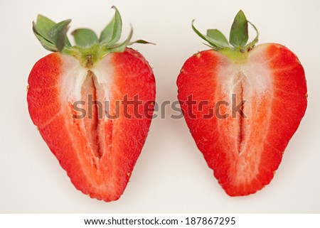 Still life of two red strawberries leaning together isolated on a white background looking tasty and attractive. Intense fruit flavors and color in organic natural healthy foods and nutritious diets.  - stock photo