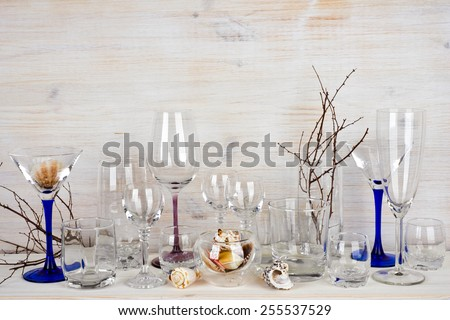 Still life of various glassware on wooden background - stock photo