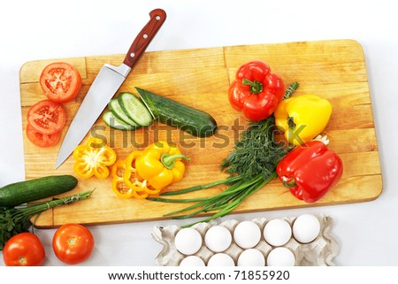 Still life of vegetables and kitchen-knife on cutting board - stock photo