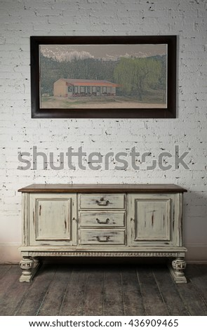 Still life of vintage white sideboard and hanged framed painting on a dark wooden floor and white bricks wall in studio - stock photo