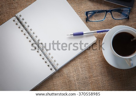still life of white paper page of note book with writing pen on table top and eye glasses hot coffee cup together - stock photo