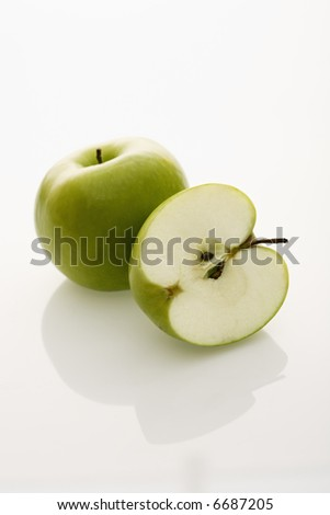Still life of whole and sliced green apples on white background.
