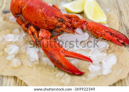 Still Life of Whole Fresh Red Lobster on Piece of Torn Brown Paper Wrapping on Rustic Wooden Table Surface - stock photo