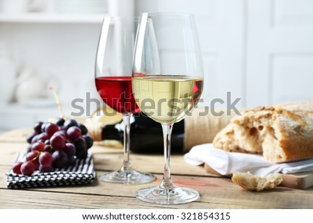 Still life of wine and bread on light background - stock photo