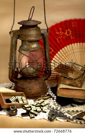 Still life - oil lamp, old photos, antique domino and jewelry - stock photo