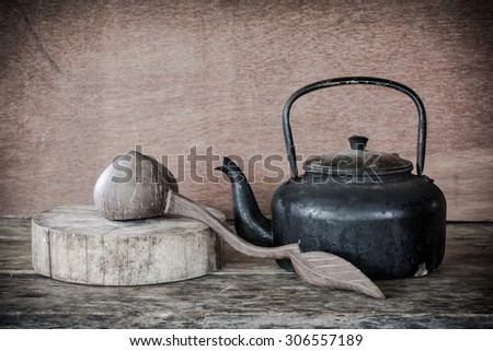 Still life old aluminium kettle and cup old-style retro on wooden background. - stock photo