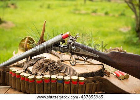 Still life, old hunting gun, hunting belt, feathers, hunting cartridges on a stump outdoors - stock photo