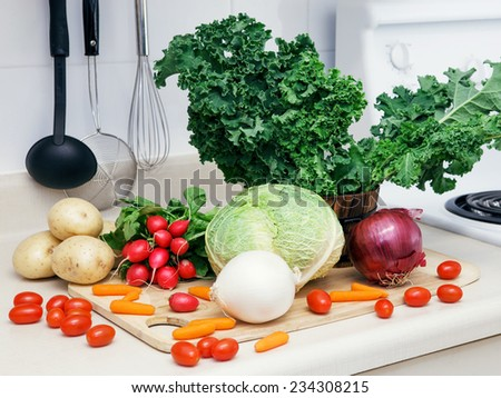 Still life on a kitchen table wooden board, ingredients for soup: green leaves of kale, red and white onion, radish, white potato, cabbage head, tomato, carrot, organic healthy food - stock photo