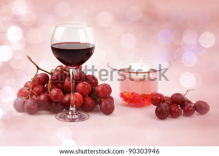 Still life on a white background glass of red wine, grapes and a candle in a decorative candlestick.