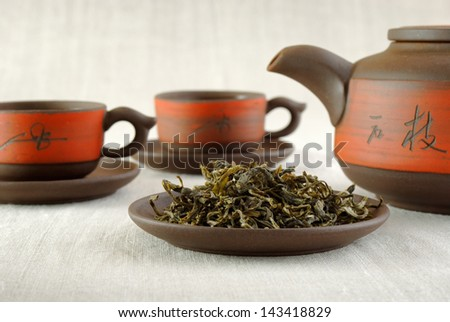 still life on canvas with tea set and dry tea - stock photo