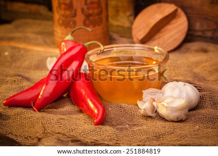 Still life on sackcloth, warm, homemade recipe. To advertise vodka, what would sober up after a hangover. Snack - red sweet ramiro pepper, honey and garlic. - stock photo