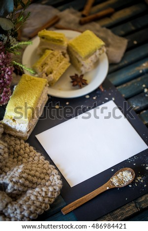 Still life on wooden table with white plate and cakes.Place for text