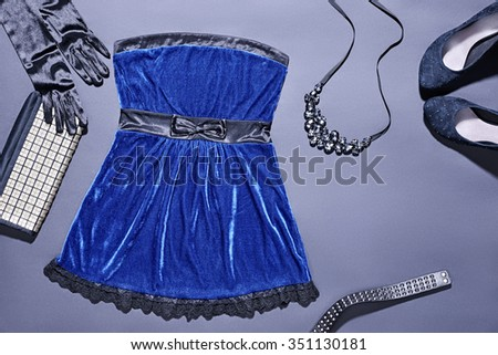 Still life Outfit  Top view. Fashion clothes stylish set, blue dress and accessories. Glamor creative, trendy black gloves, clutch, necklace, luxury shoes heels.  Unusual elegant evening party style - stock photo