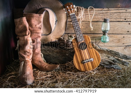 Still life painting photography with ukulele on american west rodeo brown felt cowboy hat and traditional leather boots in vintage ranch barn background - stock photo