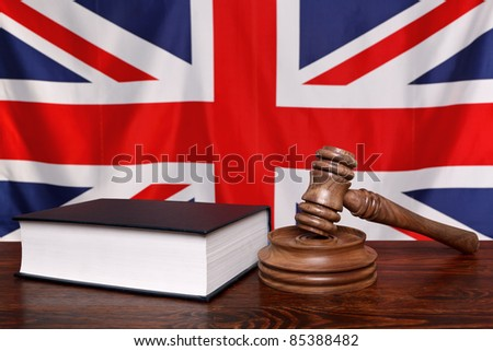 Still life photo of a gavel, block and law book on a judges bench with the United Kingdom union jack flag behind. - stock photo