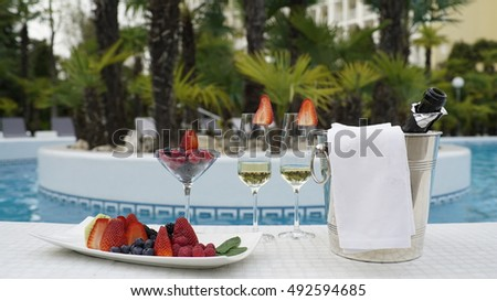 Still life photo of champangne and fruits in the pool background