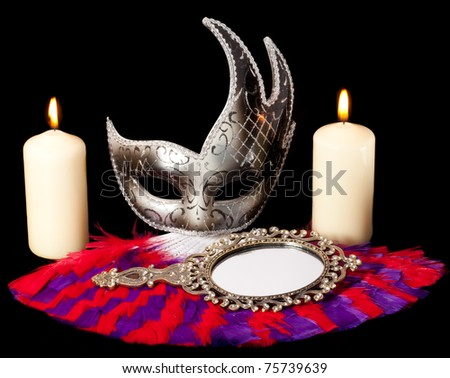 still life photo of disguise mask, mirror, fan and burning candles - stock photo