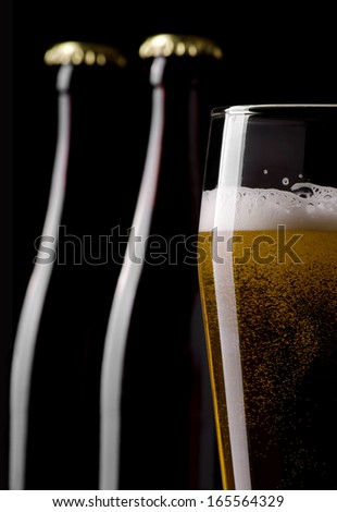 Still life photo of light lager beer and beer bottles on a background - stock photo