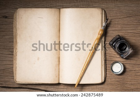 still life photography :  blank opening old book with dip pen and inkwell on old wood plank - stock photo