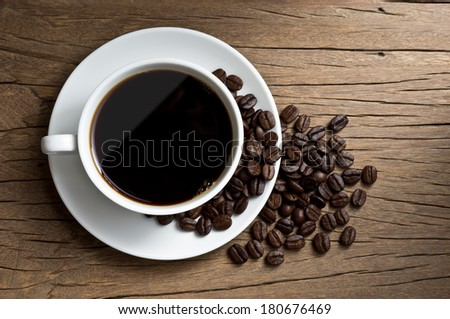 still life photography, coffee in white coffee cup and coffee beans on old wood plank - stock photo