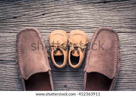 still life photography : father and child shoes on old wood in vintage color tone, go ahead together concept