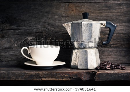 still life photography : old espresso maker with coffee beans and  white coffee cup on old wooden shelf - stock photo
