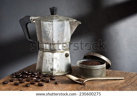 still life photography, old stove top italian espresso maker with coffee bean, coffee grind and spoon on old wood