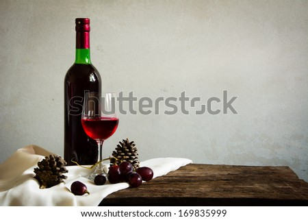 Still life Photography with Old red wine on wooden table and blue grunge background  - stock photo