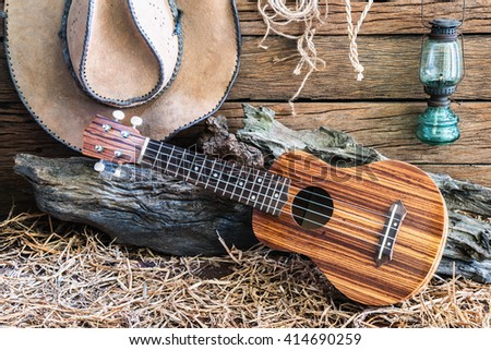 Still life photography with ukulele with american west rodeo brown felt cowboy hat and traditional in vintage ranch barn background - stock photo