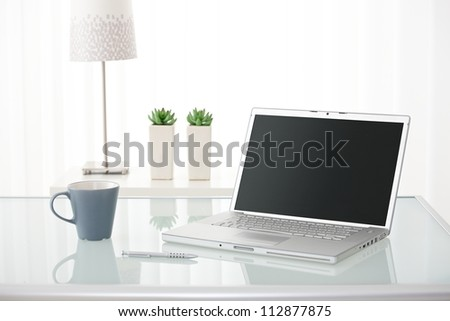 Still-life portrait of computer, pen, coffee mug on table, lamp and plants in bright environment. - stock photo