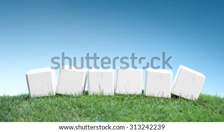 still life portrait of wooden blocks on a green grass under the bright blue sky, ready for your text - stock photo