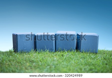 still life portrait of wooden blocks on a green grass under the bright blue sky, ready for your text