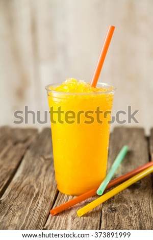 Still Life Profile of Refreshing and Cool Bright Orange Slush Drink in Plastic Cup Served on Rustic Wooden Table with Collection of Colorful Drinking Straws - stock photo