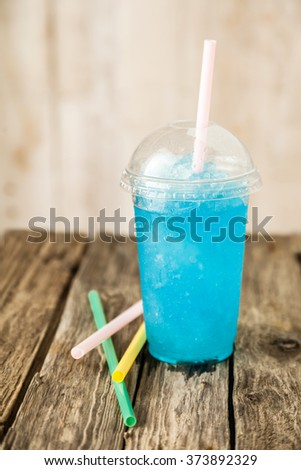 Still Life Profile View of Refreshing and Cool Frozen Turquoise Fruit Slush Drink in Plastic Cup with Lid Served on Rustic Wooden Table with Colorful Drinking Straws - stock photo