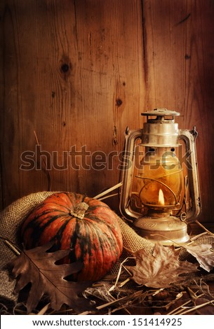Still life. Pumpkin, lighted lantern and autumn leaves. - stock photo